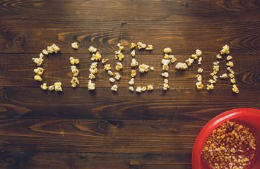 Word Cinema made of popcorn on wooden desk