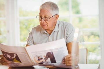 Focused senior man reading newspaper
