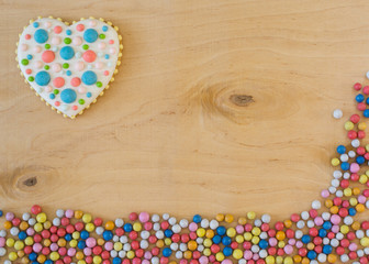 Multicolored round sugar candies and heart shaped ginger bread on natural wood background