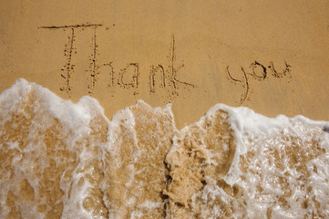 Sign Thank you on the sandy beach next to ocean