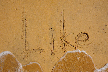 Like - text written by hand in sand on beach, with a soft wave.