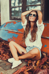 young beautiful girl hippies in sunglasses poses next to an abandoned house