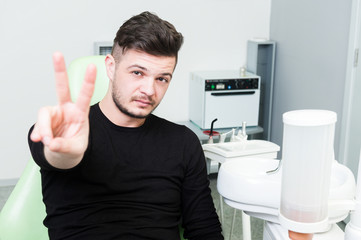 Relax patient at dentist showing peace or victory gesture