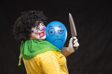 Angry ugly clown wants to kill a balloon in the cap