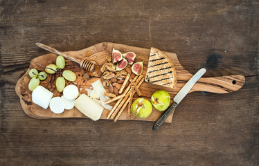Wine appetizers set: cheese selection, honey, grapes, almonds, walnuts, bread sticks, figs on olive wood serving board over rustic background, horizontal
