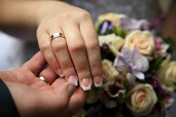 Hand in hand bride groom. Rings on background bridal wedding bouquet - Stock Image