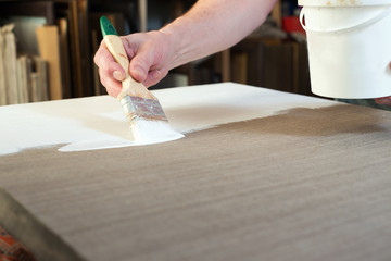An artist priming canvas
