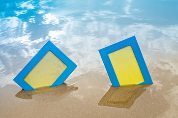Two blue blank photo frames on the sand beach