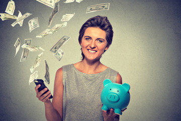 Happy woman with piggy bank and smart phone dollar banknotes bills flying away
