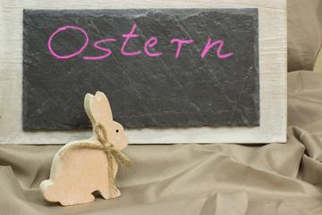 Holzosterhase vor Schiefertafel Ostern