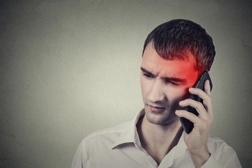 Man on the phone with headache. Cellular mobile radiation concept