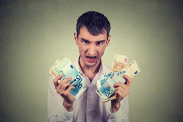 Greedy man with euro banknotes bills isolated on gray wall background