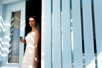 Elegant brunette bride in white dress posing near doorway with b