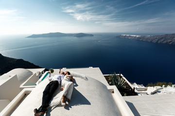 Brunette bride and groom lying on the terrace in white dress wit