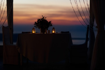 Wedding tent table and chairs lit with candles in lanterns sea b