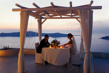 Bride and groom at sunset sitting at white table in tent sky bac