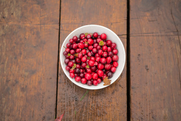 Cranberry is scattered on the grass. Autumn background. Autumn leaves.