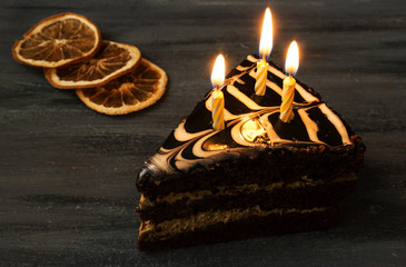 a piece of chocolate cake with candles