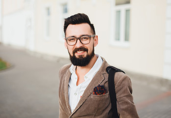 Outdoor street portrait of young fashion handsome hipster man with vintage glasses and camera,relaxing after work,weather jacket and mens accessorizes ,Hipster bearded man