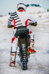 closeup racer motorcyclist during a winter race. rear view