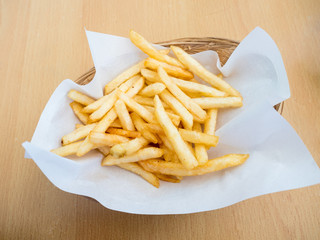 french fries in basket on wooden background