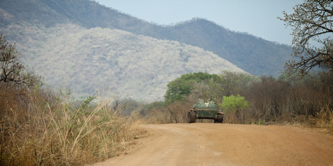 tank in road in south sudan with mountains in background