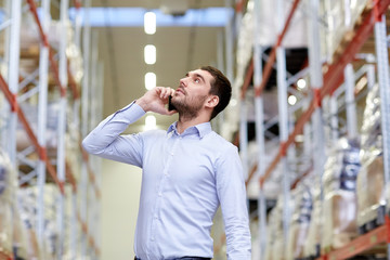 serious man calling on smartphone at warehouse