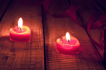 Red burning heart shaped candles on rustic wooden table.