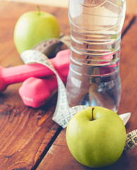 weight loss concept with tape measure organic green apple, pink dumbbels and natural bottle of sparkling water