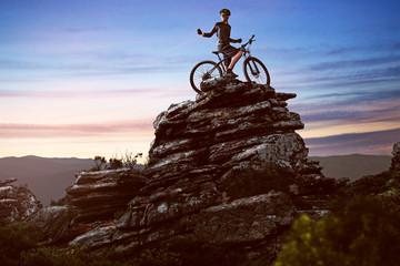 Happy biker on a big rock