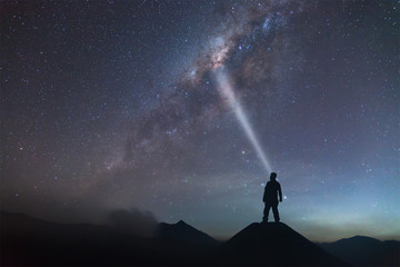 Man is standing on hill and light up to the Milky Way.