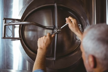 Happy brewer checking large vats