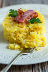 Saffron risotto garnished with bacon and parsley.