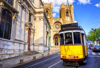 Historical yellow tram in front of the Lisbon cathedral, Lisbon,