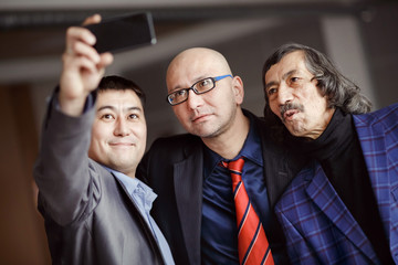 Businessmen in suits doing selfie indoors, mature. Business team of three people. Modern technology, social networking, profile picture.