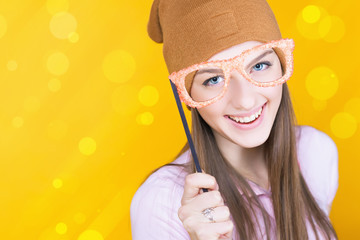 Funny teenage girl holding masquerade glasses for party
