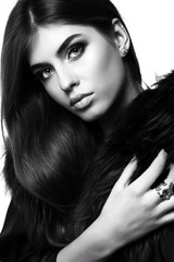 gorgeous sensual woman with dark straight hair wears elegant fur coat