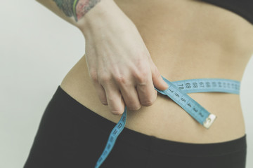 Measuring womans waist in the gym