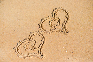Double Love hearts impression on the sand background