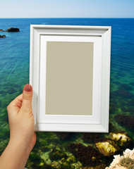 Wooden frame in woman hands on the sea background