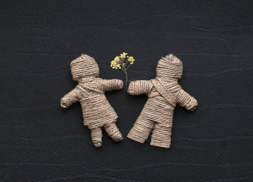 Boy and girl are made of hemp rope holding flowers. Be my valent