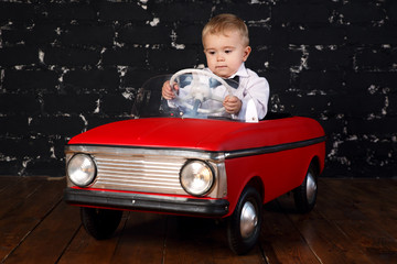 Little boy plays with big red toy car, black background