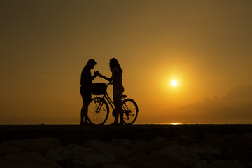 Silhouette of romantic Couple at Bali beach during sunrise. Copy Space area.