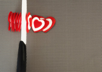 Concept. Ceramic knife cuts red hearts valentines