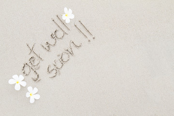 The word get well soon with white flowers on the beach surface b