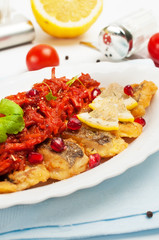 Pieces of fried fish with vegetable sauce.