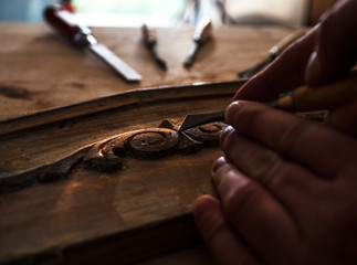 The hands of an carpenter restoring old furniture with chisel, Close-up. Dark color intensity.