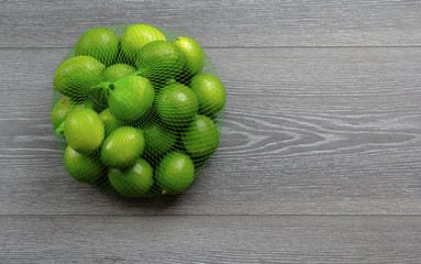 Limes in a bag on wood board background