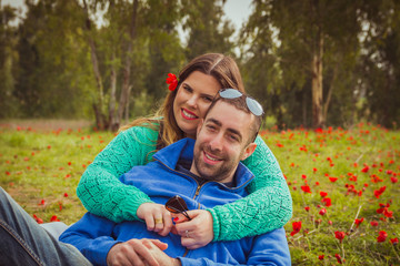 Young couple sitting on the grass in a field of red poppies and smiling at the camera