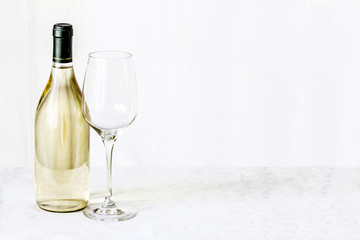 Bottle of wine and empty wineglass are stand on the white tablec